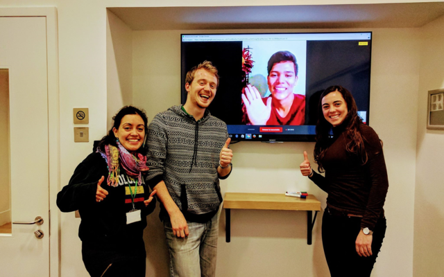 three students standing around a tv screen with a student on a virtual call.