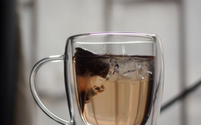 Glass mug with herbal tea in a teabag stewing inside water
