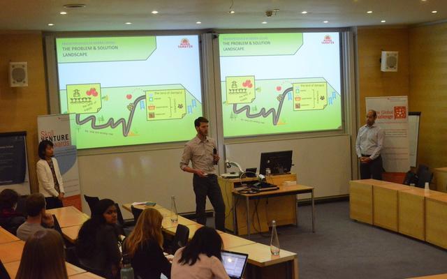 man delivering presentation in lecture theatre. Slides read 'the problem and solution landscape'