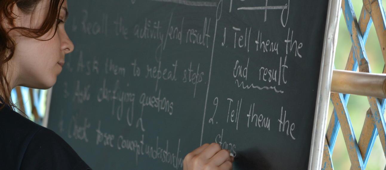 daniela writing on blackboard during a teacher training session
