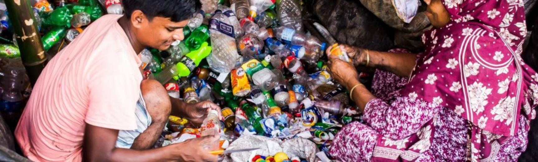 two people sifting through pile of plastic bottles