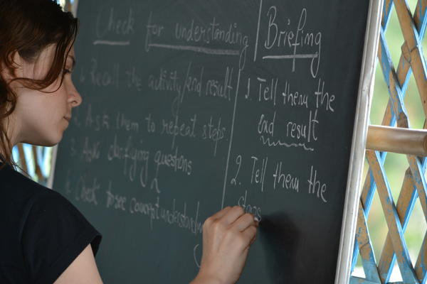daniela writing on blackboard during a teacher training session