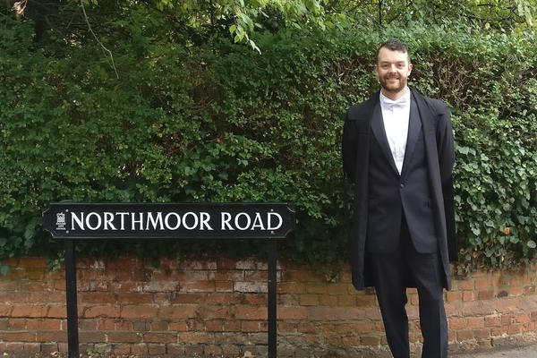 Kevin standing by the road sign for Northmoor Road in Oxford in full Oxford attire