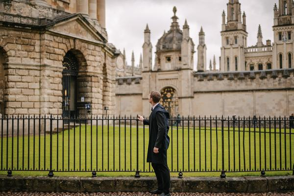 Jack Replinger stood in black traditional Oxford robes, by railings looking at the Oxford Radcliffe Camera