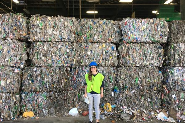 girl standing in front of blocks of rubbish