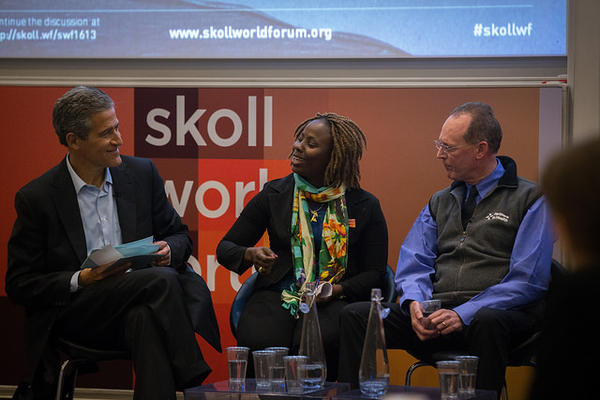 panel discussion at Skoll World Forum. Three people on a stage.