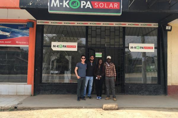 group of four people standing outside M-KOPA Solar store