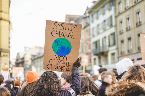 """March protest placard reading """"Systems Change not Climate Change"""" with crowd in the background"""