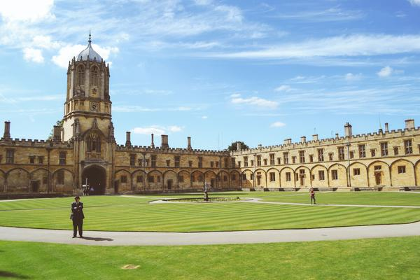 Tom Tower building in Oxford, with blue cloudy skies and green lawn.
