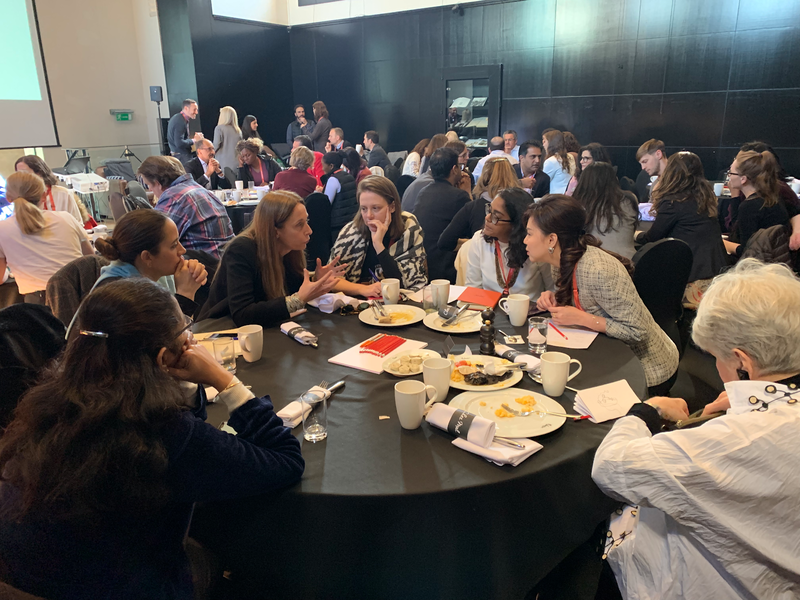 group of Skoll World Forum attendees in discussion round a table