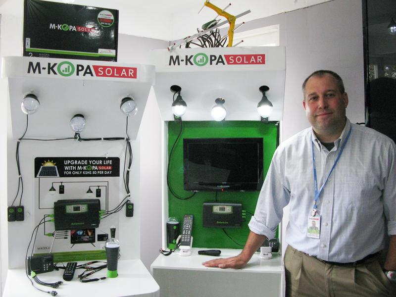 Chad Larson with M-KOPA solar light and solar TV systems.