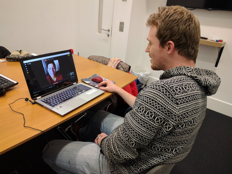 man looking at laptop screen with someone on a call