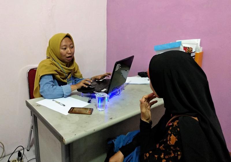 Lembaga Demografi (LD) enumerator interviewing TNF investee.